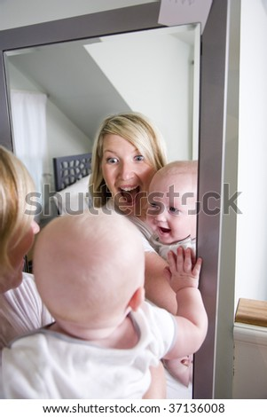 Mother and 7 month old baby playing in mirror - stock photo