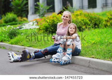 Mother and preschool daughter in roller skates - stock photo