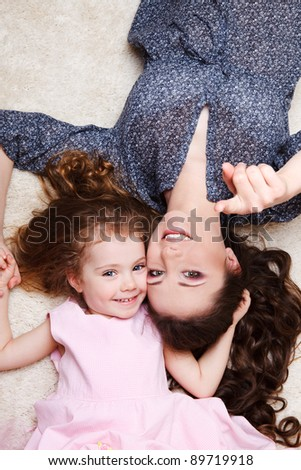 Mother and preschool girl lie on carpet - stock photo