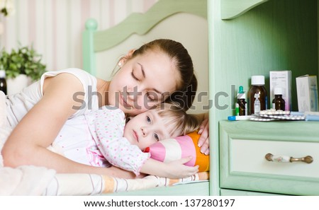 mother and sick daughter sleep together - stock photo