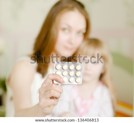 mother and sick girl - hand with pills in foreground - stock photo