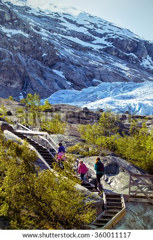 mother and sisters hiking on the lake with  mountains and the glacier Nigardsbreen at the background - stock photo