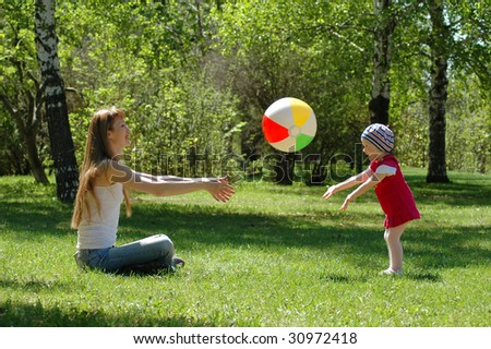 Mother and small girl game of ball - stock photo