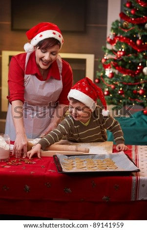 Mother and small son making christmas cake together at home.? - stock photo