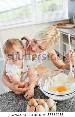 Mother and smiling child baking cookies in the kitchen - stock photo