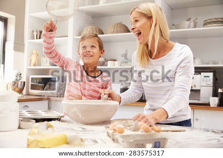 Mother and son baking together at home - stock photo