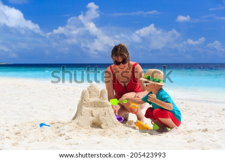 mother and son building sand castle on tropical sand beach - stock photo