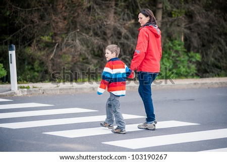 Mother and son crossing the street on the crosswalk - stock photo