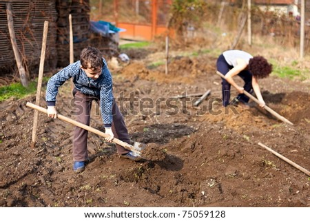 Mother and son digging into the garden for planting trees - stock photo