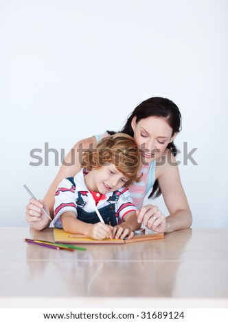 Mother and son doing homework together at home with coy-space - stock photo