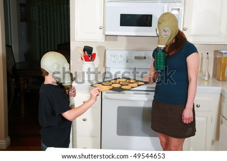 mother and son enjoy hot fresh baked cookies in their kitchen while wearing gas masks in the Future when Global Warming and CO2 have destroyed our way of living - stock photo