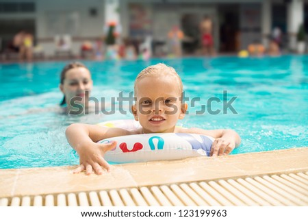 Mother and son enjoying themselves in an outdoor swimming pool - stock photo