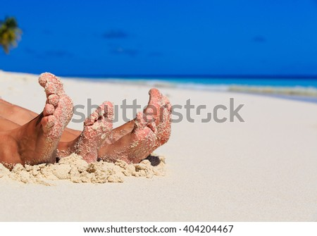 mother and son feet on summer beach - stock photo