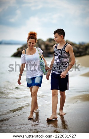 Mother and son having a walk on the beach at sunset - stock photo