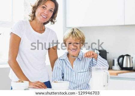 Mother and son having breakfast in kitchen - stock photo