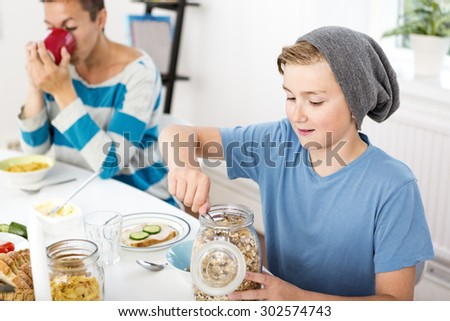 Mother and son having breakfast together in the morning - stock photo