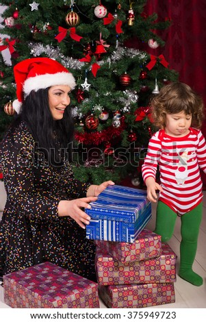 Mother and son having fun and opening Christmas presents - stock photo