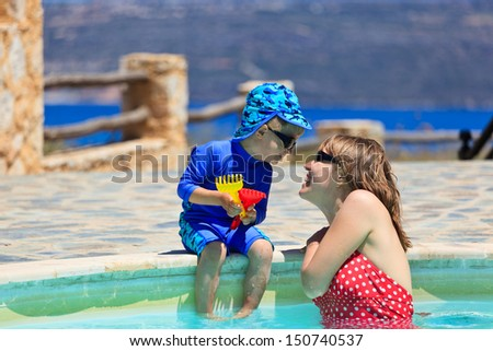 mother and son having fun at the pool - stock photo
