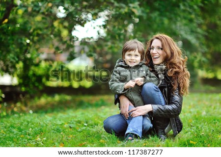 Mother and son having fun in a park - stock photo