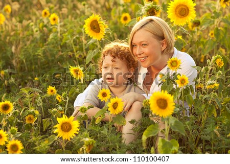 Mother and Son Having Fun in the field of sunflowers. Mother and son looking at something ahead. outdoor shot. - stock photo