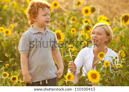 Mother and Son Having Fun in the field of sunflowers. Mother giving sunflower to her son. outdoor shot. - stock photo