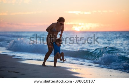 Mother and son having fun on the beach at sunset - stock photo