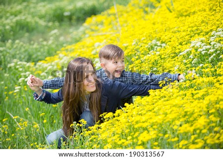 Mother and son having fun outdoors in the park. soft daylight. focus on son - stock photo