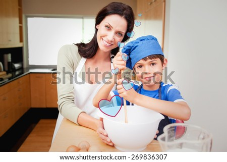 Mother and son having fun preparing dough against heart - stock photo