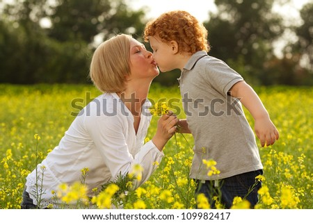 Mother and Son Having Fun. Son giving flowers to his mother and kissing her. outdoor shot. - stock photo