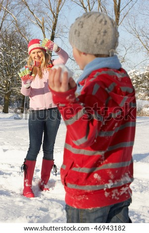 Mother And Son Having Snowball Fight In Snowy Landscape - stock photo