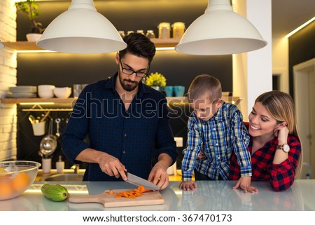 Mother and son helping father to prepare family dinner. - stock photo