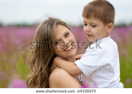 Mother and son in meadow outdoor - stock photo