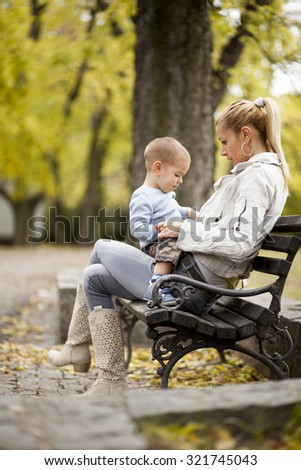 Mother and son in the autumn forest - stock photo