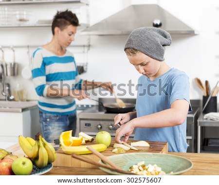 Mother and son in the kitchen preparing food together - stock photo