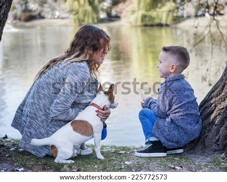 mother and son in the park with a dog, Autumn. - stock photo