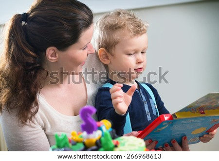 Mother and son looking at children's game - stock photo