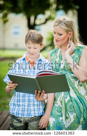 Mother and Son looking into a Book - stock photo