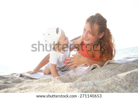 Mother and son lying on the beach and enjoy the summer day.Baby boy cuddle his mother.  - stock photo