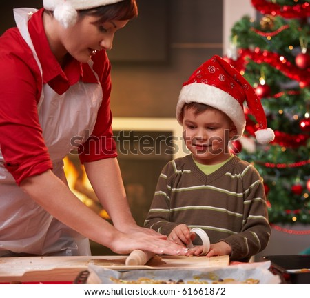 Mother and son making christmas cake, son watching mum's hand, smiling.? - stock photo