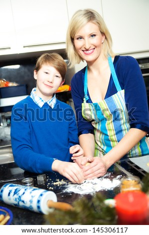 Mother and son making cookies in a kitchen - stock photo