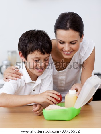 Mother and son making the school lunch in the kitchen - stock photo