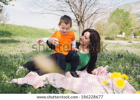Mother and son on a blanket in nature - stock photo