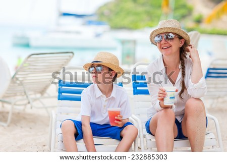 Mother and son on beach vacation enjoying drinks - stock photo