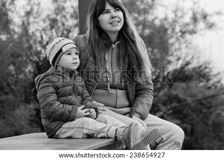 mother and son outdoors are sitting on the bench - stock photo