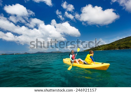 Mother and son paddling on colorful yellow kayak at tropical ocean water during summer vacation - stock photo