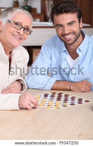 Mother and son playing draughts - stock photo