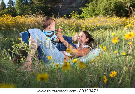 Mother and son playing in flowers in late afternoon sun - stock photo