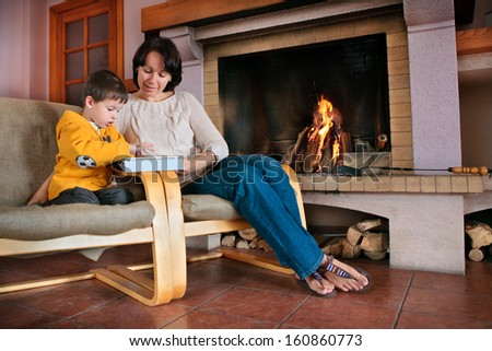 Mother and son playing on digital tablet PC - stock photo