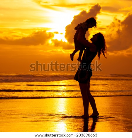 mother and  son playing on the beach at dawn time - stock photo