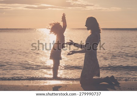 Mother and son playing on the beach at the sunset time. Concept of friendly family. - stock photo
